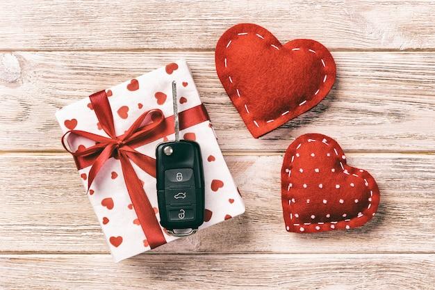 バレンタインや休日のラッパーで赤いハート、車のキー、ギフトボックスと紙で手作りのその他の休日。コピースペース、デザインの空スペースとオレンジ色の木製テーブルトップビューにボックスギフト
