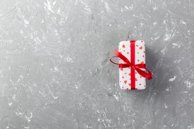 バレンタインや休日のラッパーで赤いハートとギフトボックスと紙で他の休日の手作りプレゼント。コピースペース、デザインのための空のスペースで灰色のセメントテーブルトップビューにギフトのプレゼントボックス