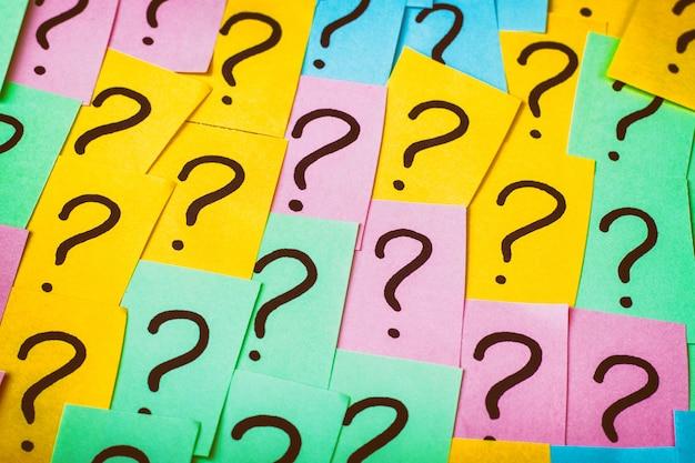 疑問符の背景。疑問符の付いたカラフルな紙のノート。コンセプトイメージ。クローズアップトップビュートーン