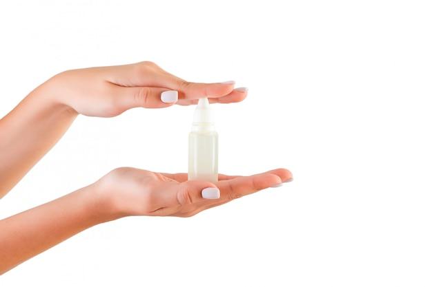 分離されたローションのクリームボトルを持っている女性の手
