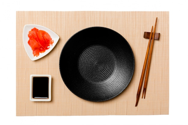 Пустая круглая черная тарелка с палочками для суши