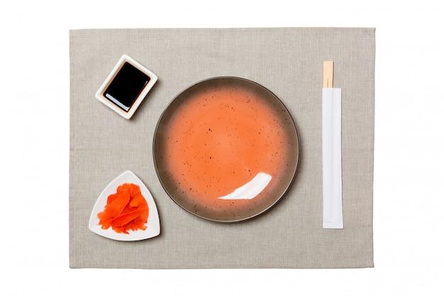 寿司の箸で空の丸い茶色のプレート