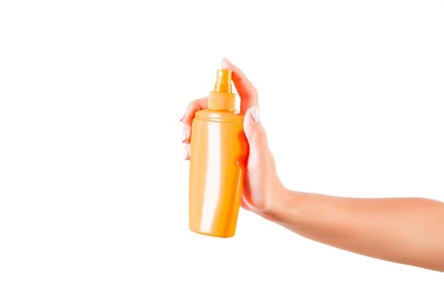 Женская рука держит кремовую бутылку