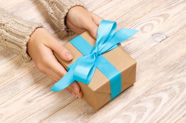 Руки женщины дарят завернутый подарок на праздник ручной работы в крафт-бумагу с голубой лентой.