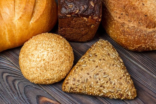 木製の表面の背景に焼きたてのパンの品揃え