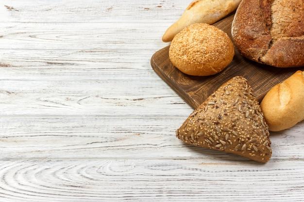 白い木製の背景にパンの盛り合わせ。コピースペース平面図