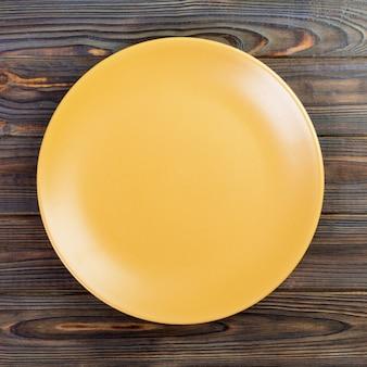 木製のテーブルに黄色の丸皿。トップビュー、デザインのテンプレート
