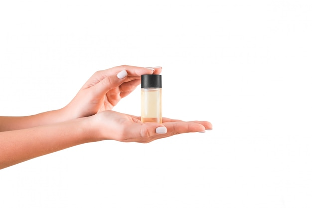 分離されたローションのクリームボトルを持っている女性の手。女の子は白のチューブ化粧品を与える