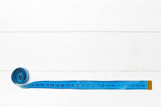 あなたのアイデアのための空のスペースを持つメジャーテープで作られた境界線フレームの平面図。木製に縫い付けてフィットさせる