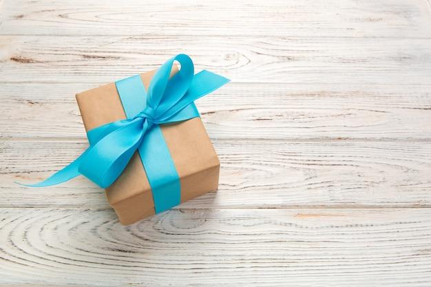 Красивая подарочная коробка с синим бантом на белом деревянном столе. вид сверху