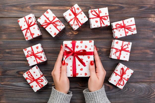 女性の手は、ラップされたバレンタインや赤いリボンと紙で他の休日の手作りプレゼントを与えます。プレゼントボックス、木製のテーブル、デザインのコピースペースと平面図上のギフトの赤いハートの装飾