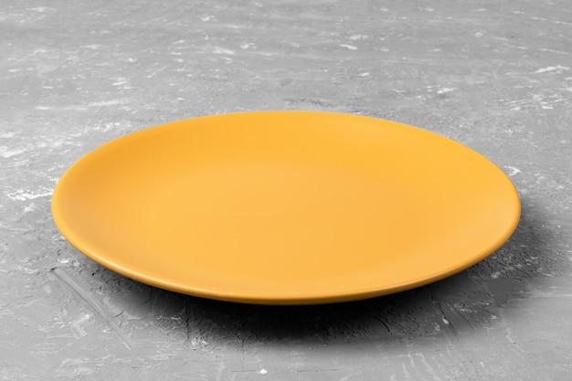 あなたの設計のための暗いセメントコピースペースにマットラウンド空のオレンジプレートの平面図です。透視図