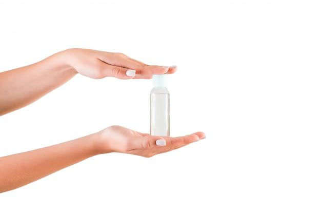 ローションのクリームボトルを持っている女性の手