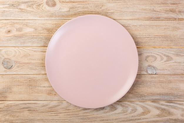オレンジ色の木製の背景上の夕食の空のバラのマット皿の上の直接
