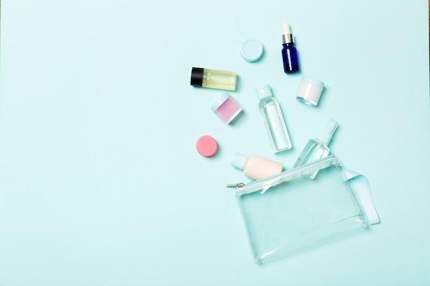 青色の背景に旅行するための小瓶のグループ。あなたのアイデアのコピースペース。化粧品の平干し組成