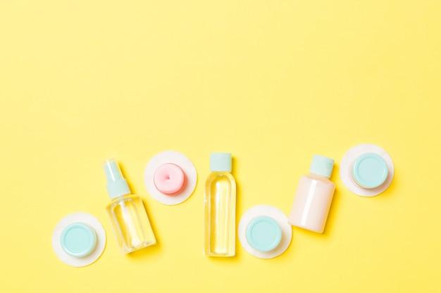 黄色の背景に旅行サイズの化粧品ボトルのセット。クリームジャーの平らな横たわっていた。ボディケアスタイルのトップビュー