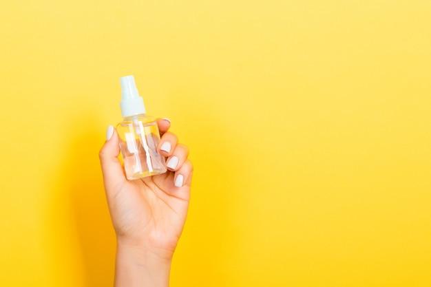 Женская рука держа бутылку сливк брызга изолированный лосьоном. девушка дает косметические продукты на желтом фоне