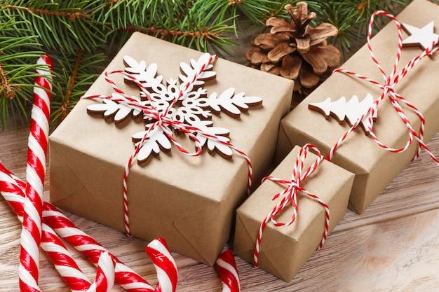 Рождественский подарок, еловые ветки и рожденственский орнамент на белом фоне. плоская планировка, вид сверху