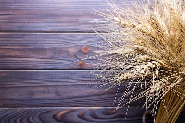 小麦の茎、木製の背景に