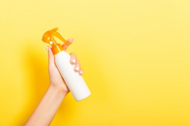 Женская рука держа бутылку сливк брызга изолированный лосьоном. девушка дарит косметические продукты на желтом