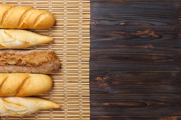 Ассорти из свежих французских багетов на деревянном столе