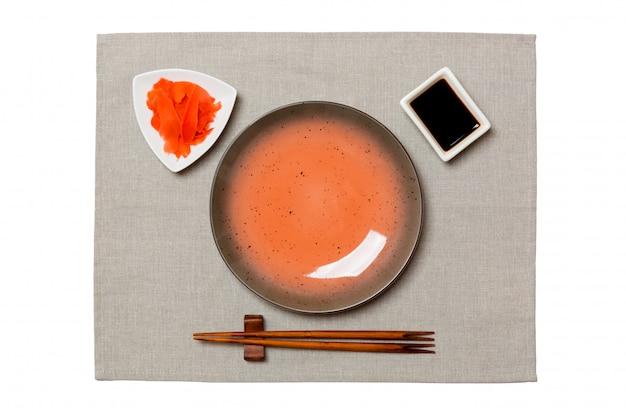 お箸で空の丸い茶色のプレート