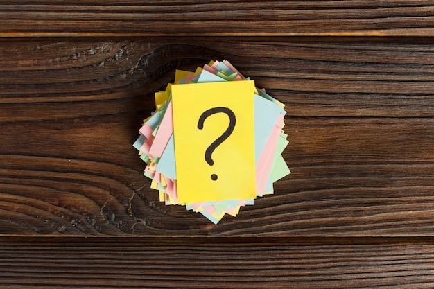 カラフルなクエスチョンマークがリマインダーチケットを書いた。質問やビジネスの概念