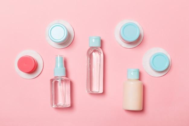 Группа маленьких бутылочек для путешествий на розовом