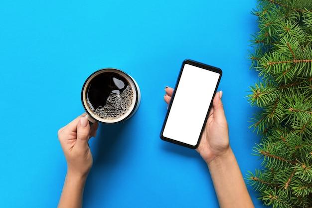 Женские руки, держа черный мобильный телефон с пустой белый экран и кружку кофе.