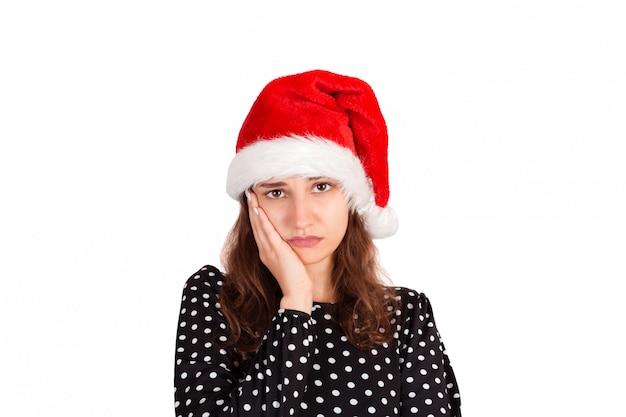 手のひらに頭をもたせて魅力的な女性にうんざり。不満からやめなさい。サンタクロースクリスマス帽子白で隔離の感情的な女の子。休日