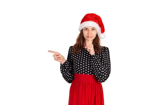 笑顔で何かを指しているドレスの若い女性。分離されたサンタクロースクリスマス帽子で感情的な女の子