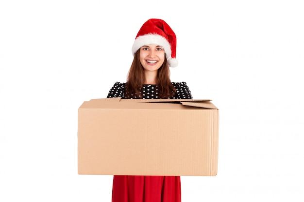 青いリボンで大きなキャロンプレゼントを与えるクリスマス帽子で陽気な幸せな女の子。孤立した