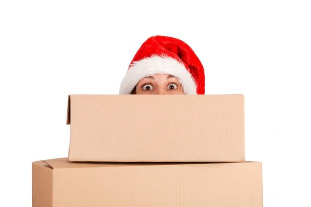 Удивленная женщина в шляпе рождества держа подарок на рождество перед лицом. изолированный