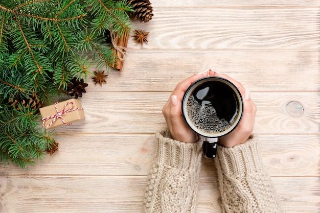 クリスマスの装飾とコーヒーキュポン木製テーブルを保持している女性の手。上面図