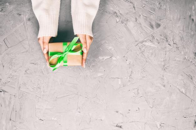 女性の手は、ラップされたバレンタインや緑のリボンと紙で他の休日の手作りプレゼントを与えます。プレゼントボックス、白いセメントテーブル、トップビューでギフトの装飾