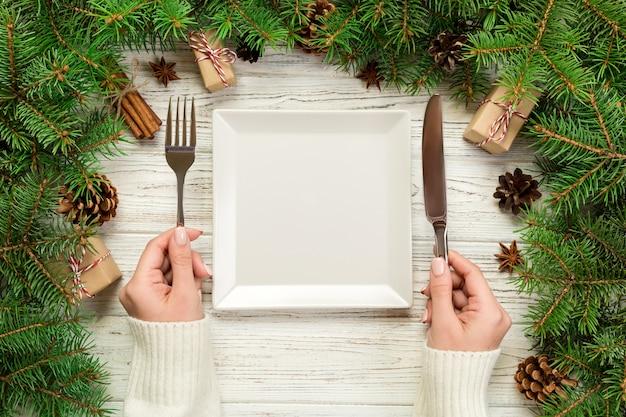 Девушка взгляд сверху держит вилку и нож в руке и готова съесть. пустая белая квадратная тарелка на деревянном рождественском украшении