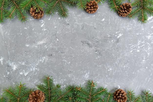 モミの木フレームとコーンコピースペースを持つクリスマスグレーセメント木製の背景。トップビューの空きスペース
