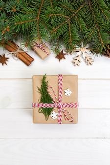 木製のテーブルにクリスマスのモミの木とギフトボックス。上面図