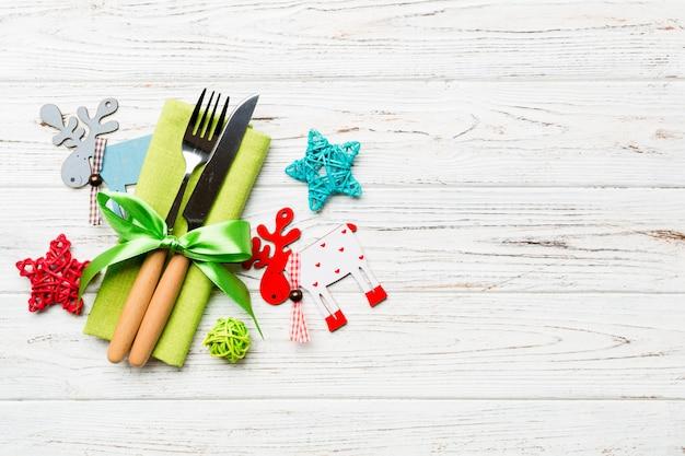 ナプキンにフォークとナイフの新年セット。クリスマスの飾りとトナカイの平面図。空のスペースで休日家族ディナーコンセプト