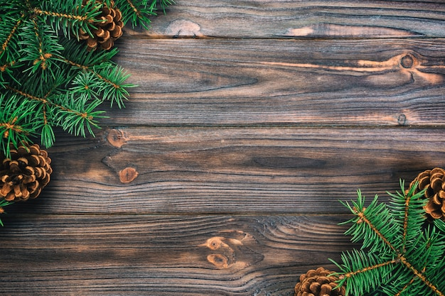 クリスマスヴィンテージ、トーンのモミの木フレームとコーンコピースペースを持つ灰色の木製の背景。トップビューの空きスペース