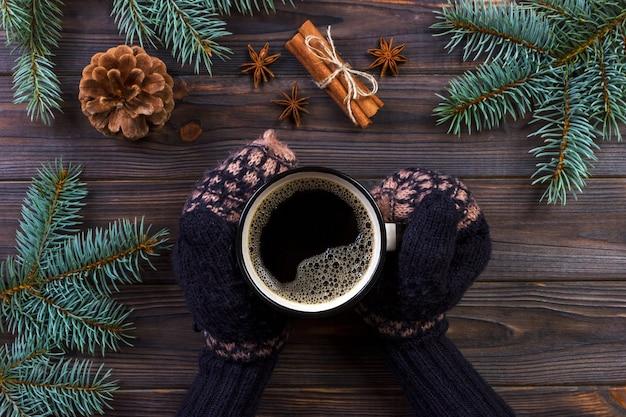 女性両手でコーヒーマグカップ、クリスマスツリーの枝、松ぼっくり、大理石のテーブル、トップビューで