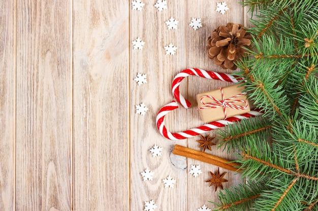 クリスマスツリーの枝、松ぼっくり、キャンディー杖お菓子、ギフト、スノーフレーク、装飾、コピースペースクリスマスの背景