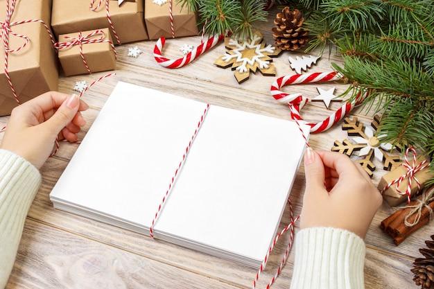 手紙のラッピングとギフトボックス、クリスマスの挨拶のカード。手紙、ギフト、クリスマスツリーの枝、クリスマスの装飾、平面図、コピースペースの封筒