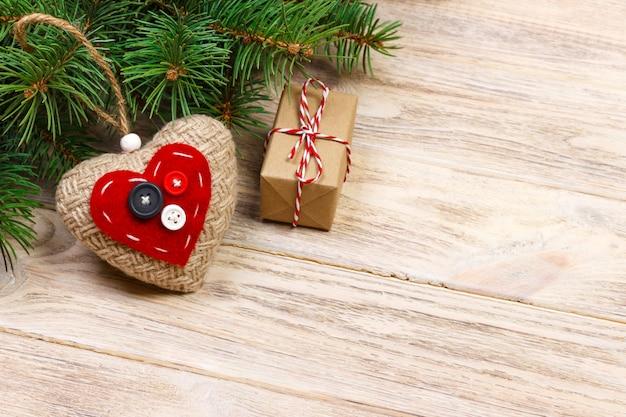 赤いギフトボックスと木製のテーブルに赤いハートのクリスマスツリーブランチ。コピースペースのトップビュー