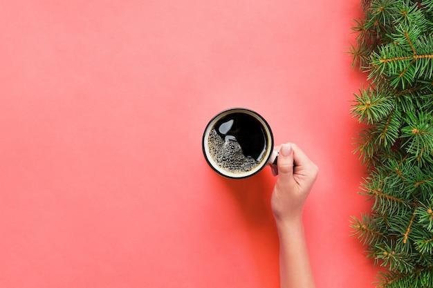 Высокий угол женщина руки, держа кружку кофе на розовом фоне минималистичный стиль. плоская планировка, вид сверху изолированный