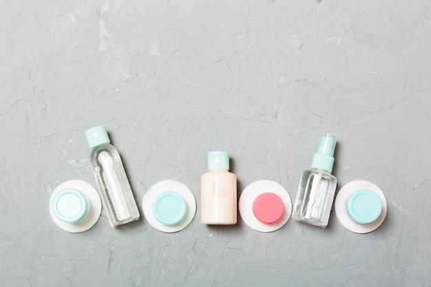 灰色の背景に旅行するための小さなボトルのグループ。あなたのアイデアのコピースペース。化粧品のフラットレイ組成。コットンパッド付きクリームコンテナーの平面図
