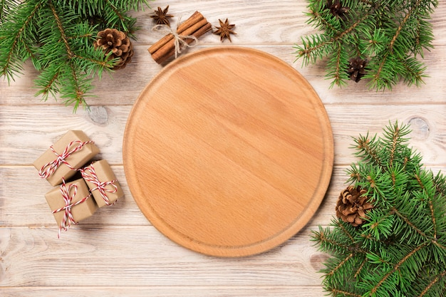 クリスマスの装飾、ラウンドボードとテーブルの背景にピザまな板。新年