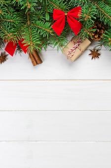 モミの木と木製のテーブルの上のギフトボックスクリスマスの背景。デザインのコピースペースを含む平面図