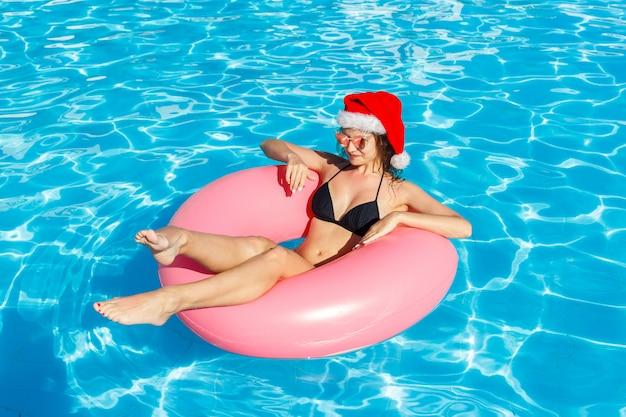 サンタクロースの帽子の若い女性のトップビュープールでピンクの円で泳ぐ