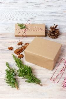 創造的な趣味。ギフト包装。サテンの赤いリボンとスタイリッシュな灰色の紙で現代のクリスマスプレゼントボックスをパッケージ化します。モミの木の枝、装飾のトップビューテーブル